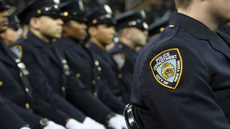 FILE- In this Dec. 29, 2014, file photo, new recruits attend their New York Police Academy graduation ceremony at Madison Square Garden in New York. (AP Photo/John Minchillo, File)