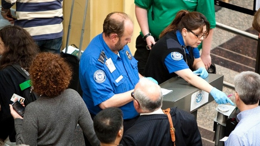 FILE: REUTERS: UNDATED: Transportation Security Administration employees check passenger IDs before they enter security screening at Reagan National Airport, outside Washington, D.C.