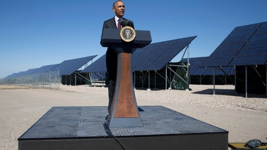 FILE - In this April 3, 2015, file photo, President Barack Obama speaks in front of a solar array at Hill Air Force Base, Utah. Obama will complete a rare presidential run though all 50 states when he delivers the commencement address at a South Dakota community college in May. (AP Photo/Carolyn Kaster, File)
