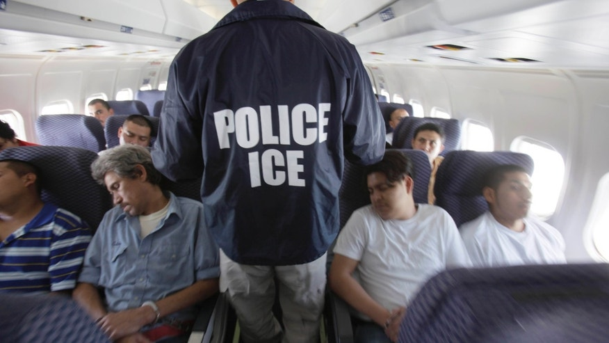May 25, 2010: An Immigration and Customs Enforcement agent walks down the aisle among shackled Mexican immigrants a boarded a U.S. Immigration and Customs Enforcement charter jet for deportation in the air between Chicago, Il.