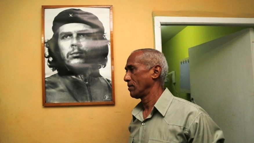 Dissident and candidate Hildebrando Chaviano walks beside a portrait of revolutionary leader Che Guevara before casting his ballot during Cuba's municipal elections at a polling station in Havana, Cuba, Sunday, April 19, 2015. Cuba held its first local elections since a historic thaw in relations with the United States with an unusual wrinkle in the single-party system: two of the 27,000 candidates openly oppose the government. (AP Photo/Desmond Boylan)