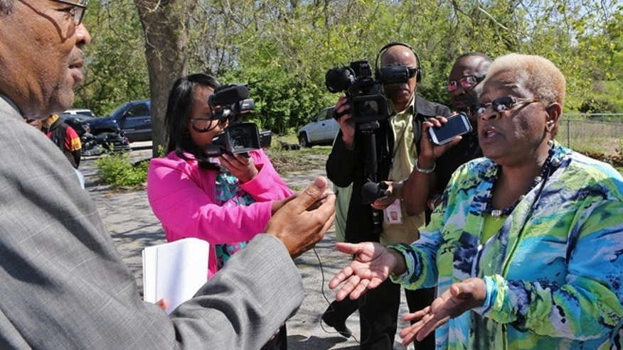 April 23, 2015: Kinloch city attorney James Robinson, left, asks Kinloch Mayor-elect Betty McCray if he can show the impeachment papers to the media at the Kinloch City Hall, in Kinloch, Mo. (AP_