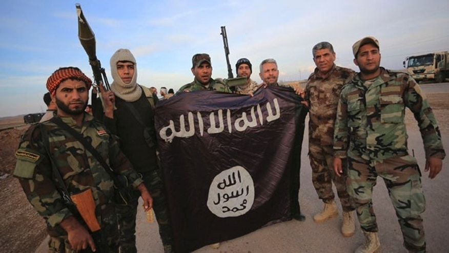FILE: Nov. 23, 2014: Iraqi Shite fighters with an Islamic State flag that they pulled down on the front line in Jalawla, Diyala province of Iraq.