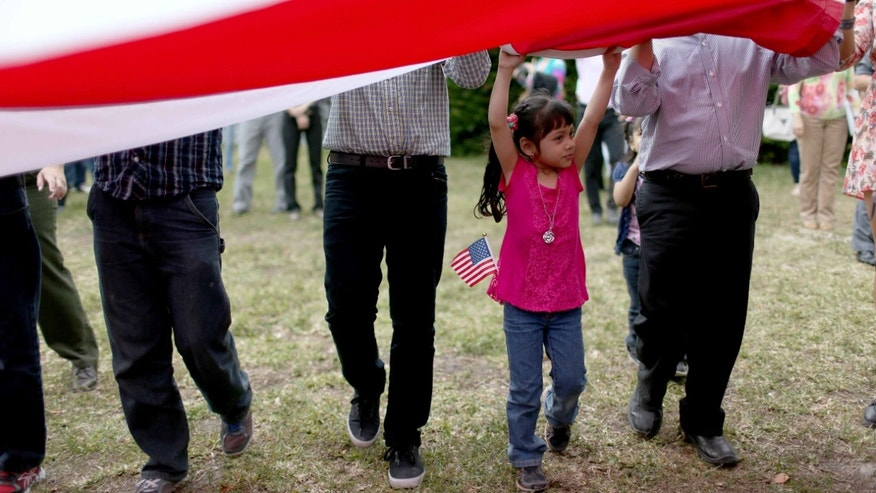 HOMESTEAD, FL - FEBRUARY 17:  Alexandra Rodelo, 5, helps with an American flag after she watched her brother sworn in as a United States citizen during a naturalization ceremony put on by the U.S. Citizenship and Immigration Services at the Biscayne National Park on February 17, 2015 in Homestead, Florida. The ceremony saw roughly 150 people, primarily children, sworn in from countries around the globe such as China, Philippines and Cuba, among others.  (Photo by Joe Raedle/Getty Images)