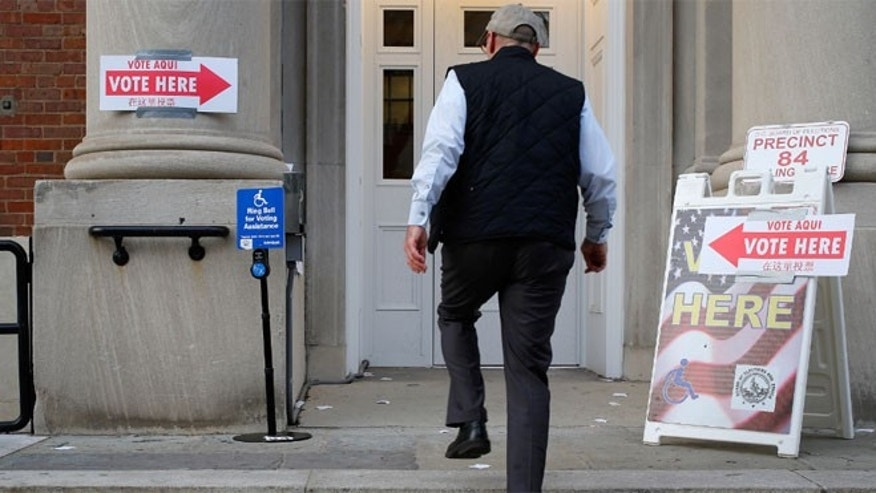 FILE: Nov. 4, 2014: A voter enters the polling place at Stuart-Hobson Middle School on Capitol Hill, in Washington, D.C.