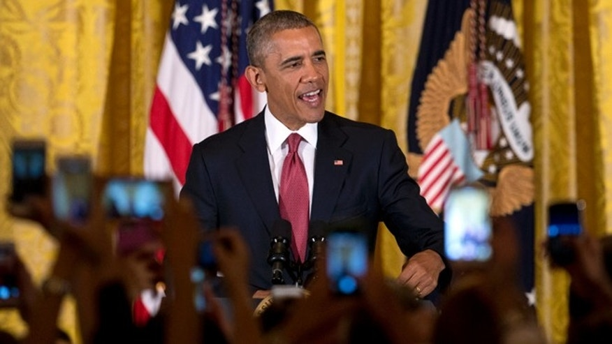 Audience members hold their cell phones high as President Barack Obama speaks during a Cinco de Mayo reception in the East Room of the White House in Washington, Tuesday, May 5, 2015. Obama says that when it comes to achieving a comprehensive overhaul of immigration laws progress is 'not always a straight line.' He says that despite his executive actions on immigration, Congress still needs to pass legislation to make more permanent changes. (AP Photo/Carolyn Kaster)