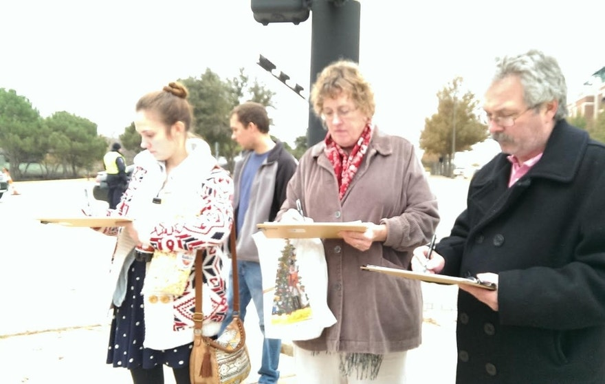 Voters in Arlington are seen signing the anti-camera petition started by Canon and Bussey.