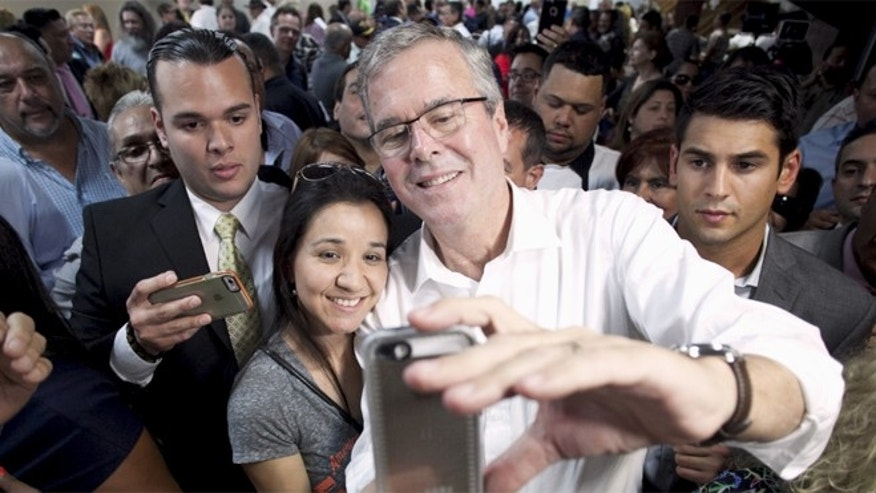 FILE: April 28, 2015: Probable 2016 GOP presidential candidate and former Florida Gov. Jeb Bush (white shirt) poses for a selfie during a town hall meeting in San Juan, Puerto, Rico.