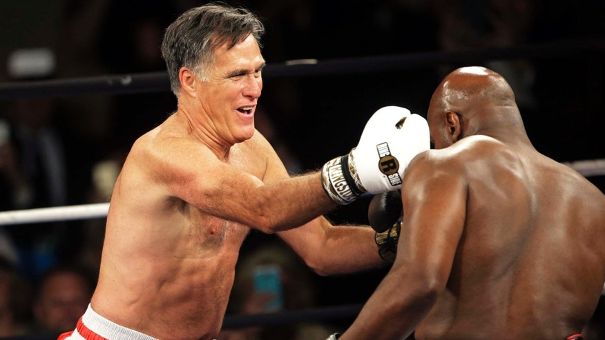 May 15, 2015: Former Republican presidential candidate Mitt Romney, left, lands a punch against five-time heavyweight boxing champion Evander Holyfield at a charity fight night event.