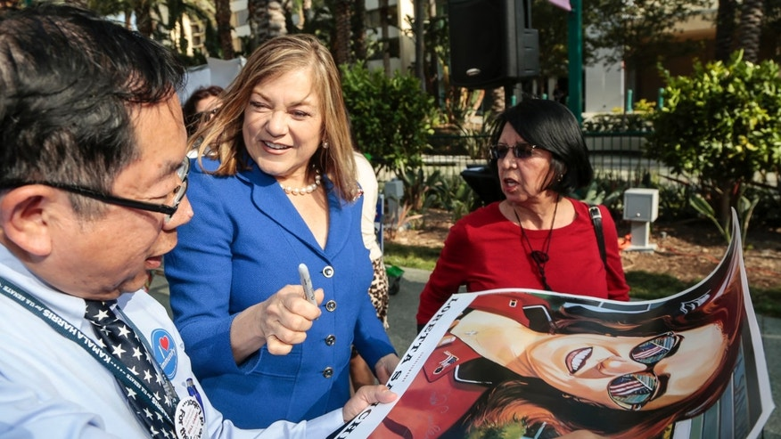 California Rep. Loretta Sanchez, second from left, autographs a California Senate race campaign poster to an unidentified supporter at the California Democrats State Convention in Anaheim, Calif., on Saturday, May 16, 2015. (AP Photo/Damian Dovarganes)