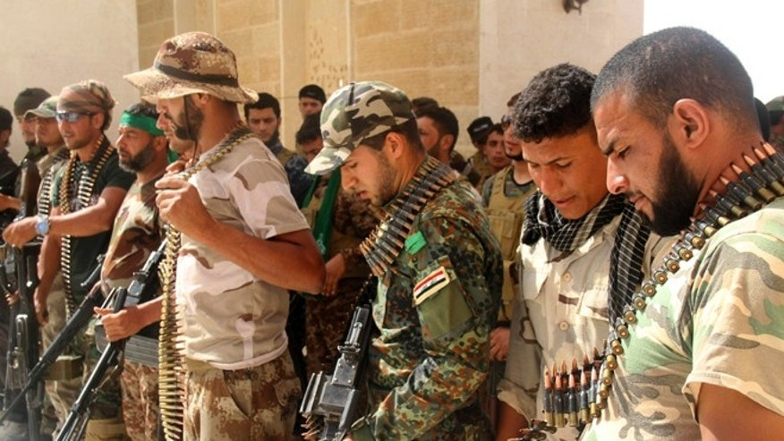 FILE: May 21, 2015: Iraqi Shiite militiamen check their weapons against ISIS, in the predominately Sunni city of Nukhayb, in southwest Iraq.