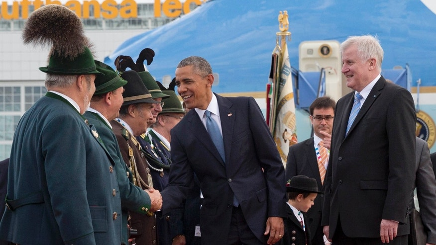 June 7, 2015: US President Barack Obama, joined by Horst Seehofer, Minister President of Bavaria, right, is greeted by traditionally dressed Bavarian men and women as he arrives on Air Force One at the airport in Munich, southern Germany.
