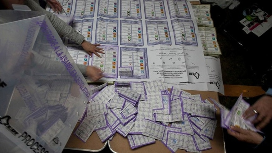 Electoral volunteers count ballots after the polls closed in the country's midterm elections at a polling station in Mexico City, Sunday, June 7, 2015. The incident comes on the day of the mid-term elections as a loose coalition of radical teachers' unions and activists vowed to block the vote for 500 seats in the lower house of Congress, nine of 31 governorships and hundreds of mayors and local officials. (AP Photo/Marco Ugarte)