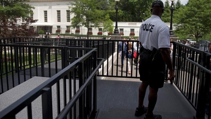 June 9, 2015: A member of the Secret Service Police looks toward the West Wing of the White House in Washington during an evacuation of the media area of the White House because of a bomb threat. (AP Photo/Carolyn Kaster)