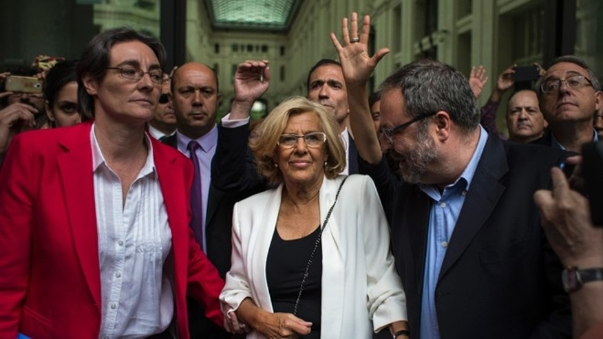 Madrid's new Mayor and member of Ahora Madrid (Madrid Now) party, Manuela Carmena, centre, meet the crowd in Madrid, Spain, Saturday, June 13, 2015. Spain's biggest cities, Madrid and Barcelona, are expected to swear in far-left mayors Saturday, and the radical leaders promise to cut their own salaries, halt homeowner evictions and eliminate perks enjoyed by the rich and famous. (AP Photo/Andres Kudacki)