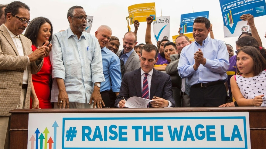 June 13, 2015: Los Angeles Mayor Eric Garcetti, center, joins members of the City Council and community leaders as he signs into law an ordinance that will gradually raise the minimum wage to $15 an hour by 2020, in at Martin Luther King Jr. Park in Los Angeles.