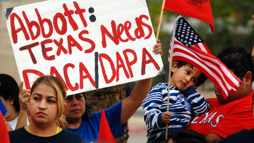 Over 100 hundred people demonstrated in front of the Federal Courthouse in Brownsville, Texas, Thursday, March 19, 2015. The Justice Department might face sanctions if a federal judge determines its attorneys misled him about whether part of President Barack Obama's executive action on immigration was implemented prior to it being put on hold by the judge. U.S. District Judge Andrew Hanen last month halted Obama's plan. The president's plan would spare from deportation up to 5 million people in the U.S. illegally. (AP Photo/Brownsville Herald, Brad Doherty)