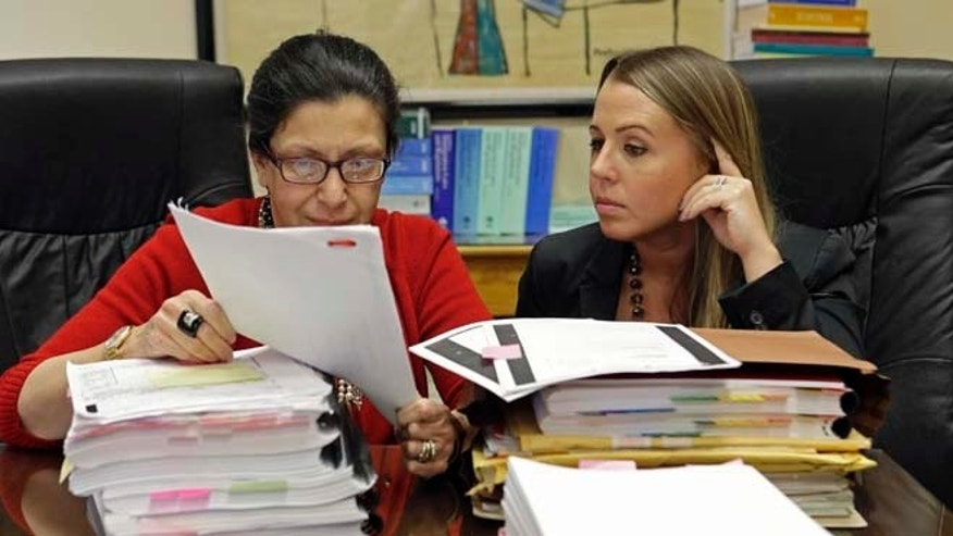 Attorneys Grisel Ybarra and Monica Barba Neumann look over documents at their office in Miami, on July 16, 2015.