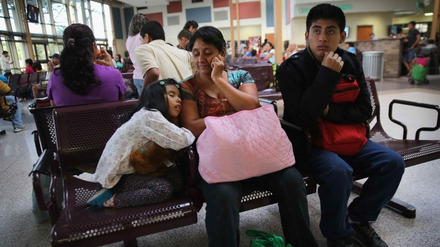 A Guatemalan family waits at the Greyhound bus station before their trip to Maryland on July 25, 2014 in McAllen, Texas.