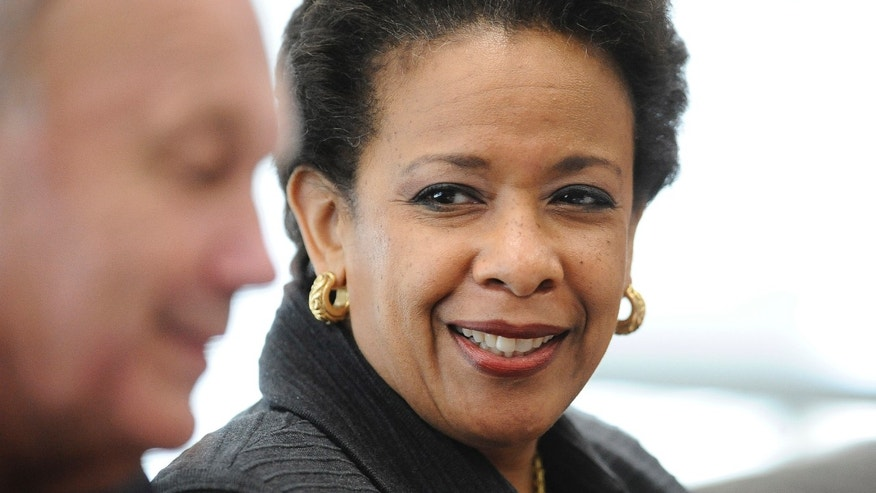 U.S. Attorney General Loretta Lynch listens to East Haven Police Chief Brent Larrabee, left, speak during a community policing tour, Tuesday, July 21, 2015, in East Haven, Conn. Lynch is in Connecticut to highlight improvements in relations between police and Latinos since four officers were arrested in 2012 on abuse charges. (AP Photo/Jessica Hill)