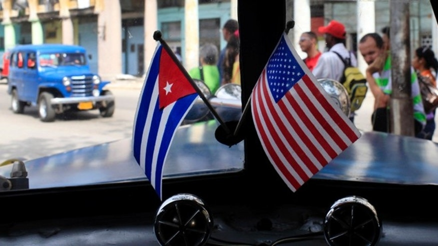 Miniature flags representing Cuba and the U.S. are displayed on the dash of an American classic car in Havana, Cuba, Friday, March 22, 2013. U.S. Secretary of State John Kerry must decide within a few weeks whether to advocate that President Barack Obama should take Cuba off a list of state sponsors of terrorism, a collection of Washington foes that also includes Iran, Syria and Sudan. Cuban officials have long seen the terror designation as unjustified and told visiting American delegations privately in recent weeks that they view Kerry's recommendation as a litmus test for improved ties. (AP Photo/Franklin Reyes)
