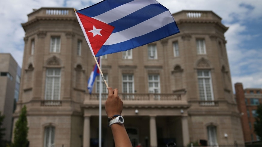 A supporter waves a Cuban flag in front of the country's embassy in D.C. after it re-opened on July 20, 2015.
