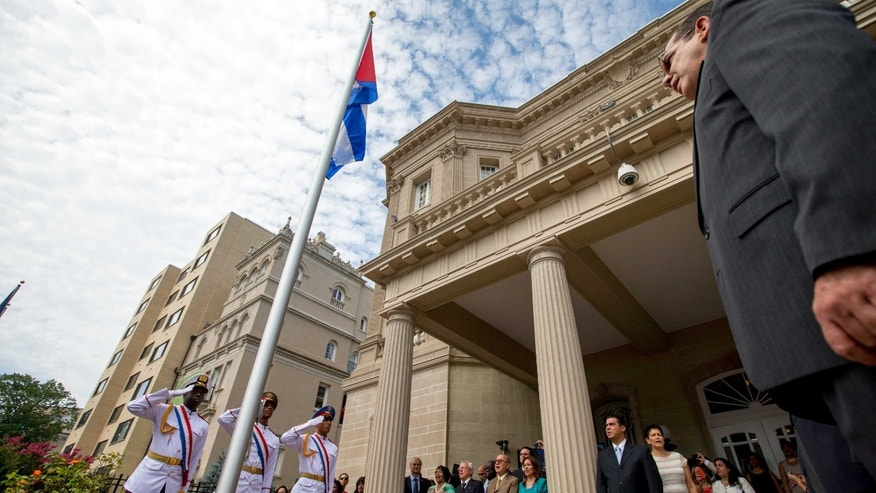 Cuban Foreign Minister Bruno Rodriguez, right, stands and faces the Cuban flag after raising it over their new embassy in Washington, Monday, July 20, 2015. Cuba's blue, red and white-starred flag was hoisted Monday at the country's embassy in Washington in a symbolic move signaling the start of a new post-Cold War era in U.S.-Cuba relations. (AP Photo/Andrew Harnik, Pool)