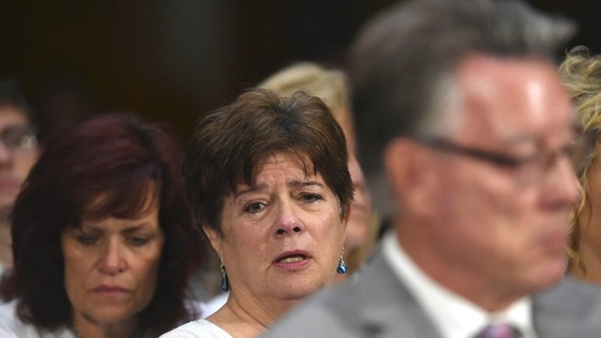 FILE - In this July 21, 2015, file photo, Liz Sullivan, mother of Kathryn Steinle, who was killed on a San Francisco Pier, allegedly by a man previously deported several times, listens to testimony behind Jim Steinle during a Senate Judiciary hearing to examine the Administration's immigration enforcement policies, in Washington. Since the fatal shooting of Steinle, the debate over how to handle cities and counties that refuse to cooperate with immigration authorities has reached a feverish pitch. (AP Photo/Molly Riley, File0