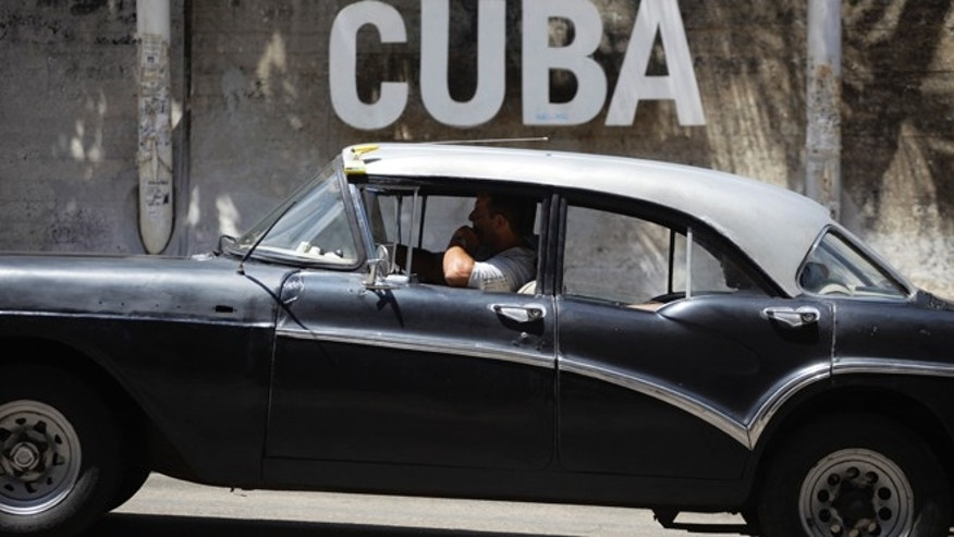 "A man drives his taxi past a Cultural Center with the word ""Cuba"" on it, in Havana, Cuba."