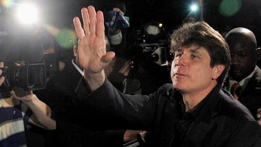 FILE - In this March 15, 2012 file photo, former Illinois Gov. Rod Blagojevich waves as he departs his Chicago home for Littleton, Colo., to begin his 14-year prison sentence on corruption charges. (AP Photo/Charles Rex Arbogast, File)