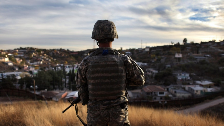 "NOGALES, AZ - DECEMBER 07:  An Arizona National Guardsman watches over the U.S. border with Mexico at an observation post on December 7, 2010 in Nogales, Arizona. The Obama administration ordered more than 500 soldiers placed along the Arizona border to man ""entry identification sites"" and spot illegal immigrants crossing into the United States. The troops, who have no detention authority, radio U.S. Border Patrol agents when they spot immigrants crossing. The troop deployment was meant to further bolster border security and help stem illegal immigration into Arizona, which has become a flashpoint for the issue nationwide.  (Photo by John Moore/Getty Images)"