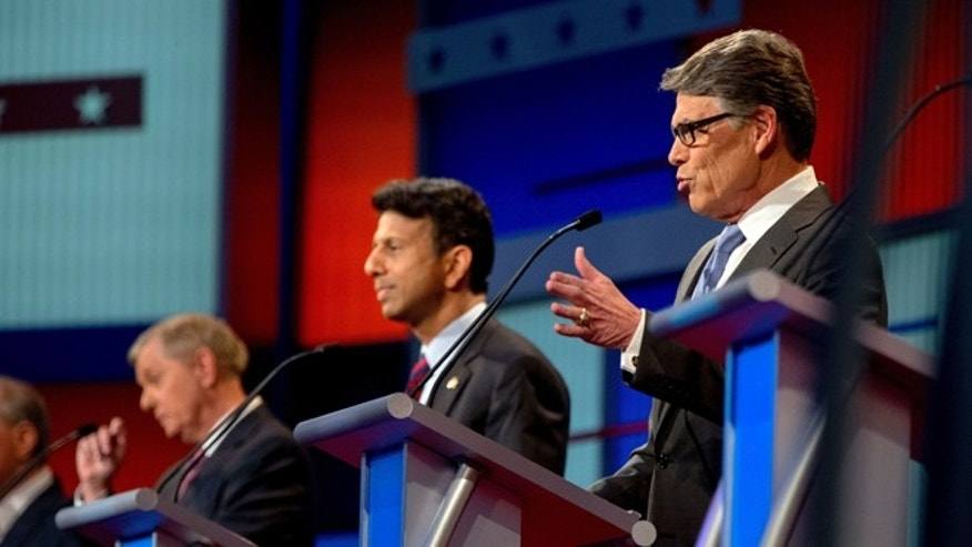 Republican presidential candidate former Texas Gov. Rick Perry, right, speaks during a pre-debate forum at the Quicken Loans Arena, Thursday, Aug. 6, 2015,  in Cleveland. Seven of the candidates have not qualified for the primetime debate. (AP Photo/Andrew Harnik)