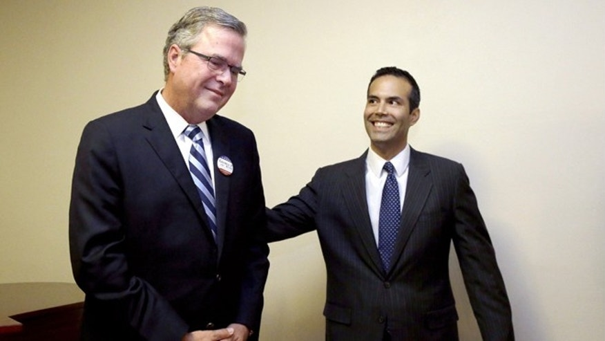 File - In this Oct. 4, 2014 file photo, George P. Bush, right, reaches to his father former Florida Gov. Jeb Bush after the senior Bush became emotional when expressing his pride for his son while speaking to supporters at Hardin-Simmons University, in Abilene, Texas. George P. Bush has been helping members of his famous family get elected since age 3 but has never played a larger role as a political surrogate than this cycle, as he tries to help his dad follow his grandfather, George H.W. Bush, and his uncle, George W. Bush, to the White House.  (AP Photo/LM Otero, File)