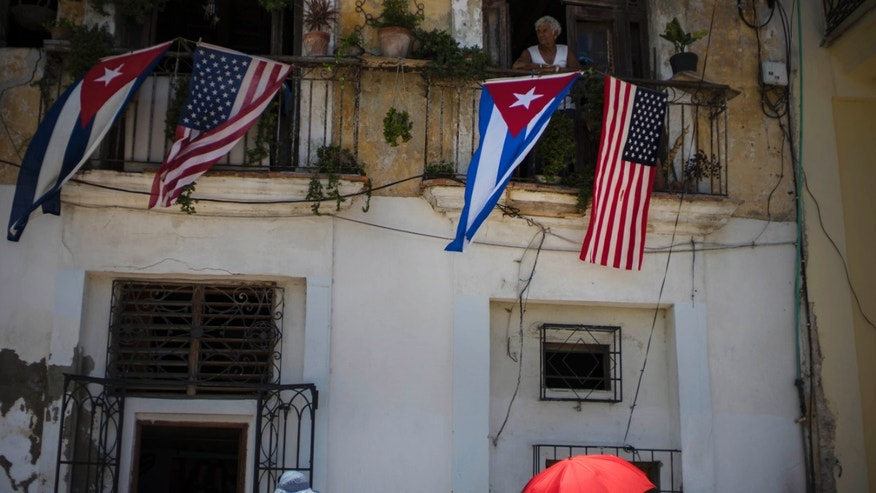 Cuban and U.S. flags hang from a resident's balcony on the day the U.S. opened its embassy in Havana, Cuba, Friday, Aug. 14, 2015. U.S. Secretary of State John Kerry and his Cuban counterpart Bruno Rodriguez said their nations would continue to disagree over issues such as democracy and human rights. But they also said they hoped to make progress on issues ranging from maritime security and public health to the billions of dollars in dueling claims over confiscation of U.S. property and the U.S. economic embargo on the island. (AP Photo/Ramon Espinosa)