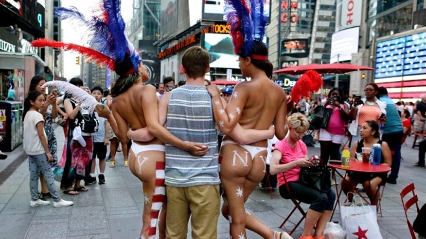 July 28, 2015: a tourist poses for a photo with two women clad in thongs and body paint in Times Square, in New York. (AP)