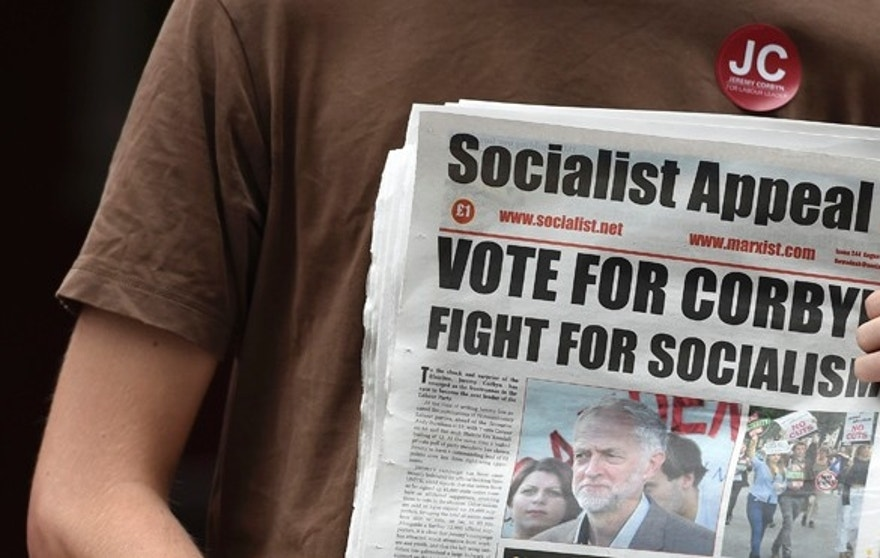 Aug 8, 2015: An activist holds a political paper as British Labor Party politician Jeremy Corbyn arrives for a community meeting in north London. (Reuters)