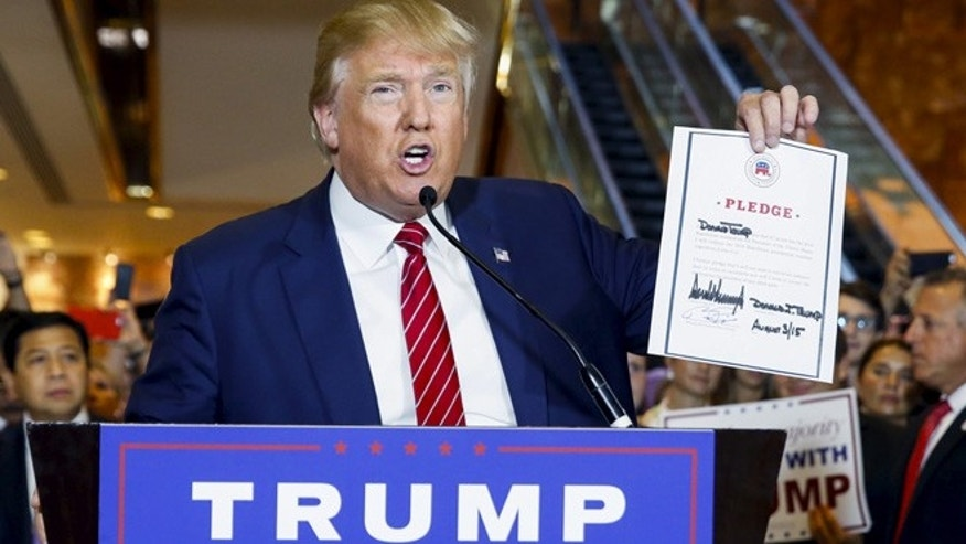 Sept. 3, 2015: U.S. presidential hopeful Donald Trump holds up a signed pledge during a press availability at Trump Tower in Manhattan, New York. (Reuters)