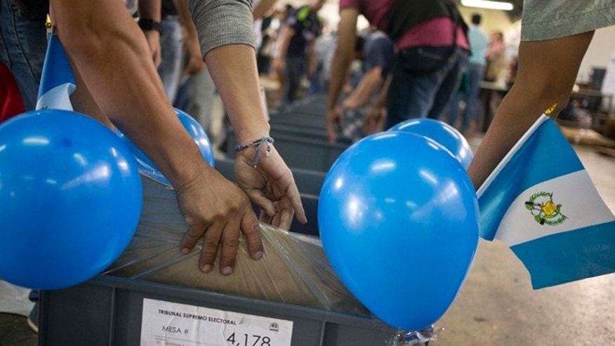 Electoral workers prepare the last box of voting materials for polling stations, decorated with Guatemalan flags and balloons in Guatemala City, Saturday, Sept. 5, 2015. Voters go to the polls Sunday for normally scheduled general elections, less than a week after Otto Perez Molina resigned as president. (AP Photo/Esteban Felix)