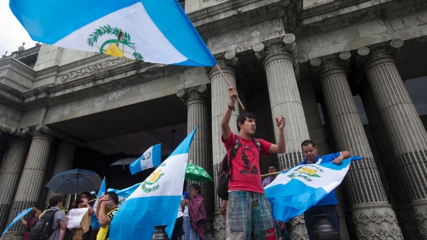 Guatemalans wave national flags as they celebrate the resignation of President Otto Perez Molina, in Guatemala City, Thursday, Sept. 3, 2015. Guatemala's new president, Alejandro Maldonado was sworn in Thursday afternoon, amid a corruption scandal that has caused a national political crisis. The conservative former judge will serve out the term of Perez Molina, who resigned late Wednesday. (AP Photo/Esteban Felix)