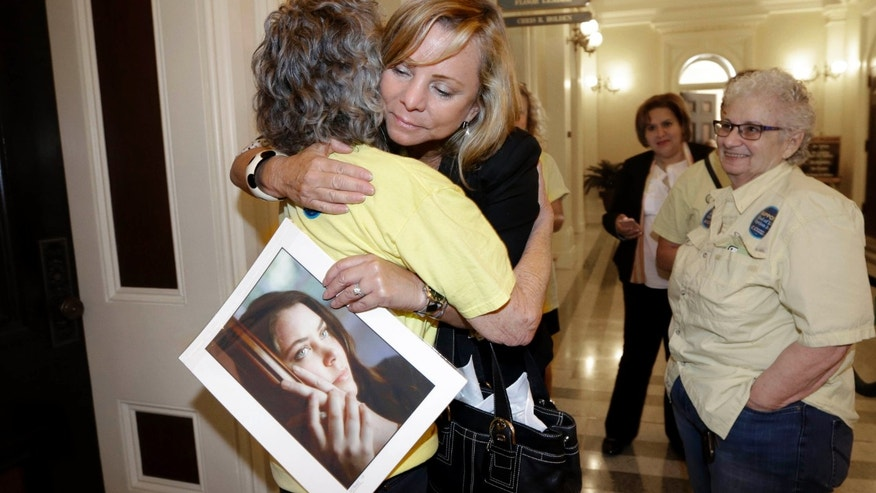 Sept. 9, 2015: Debbie Ziegler holds a photo of her daughter, Brittany Maynard, as she receives congratulations from Ellen Pontac, after a right-to die measure was approved by the Assembly in Sacramento, Calif.