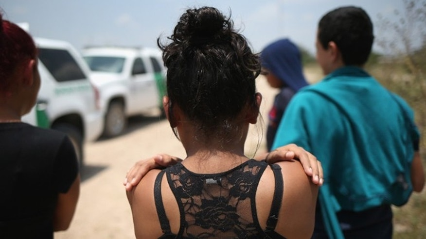 MISSION, TX - JULY 24:  Unaccompanied minors from El Salvador await transport to a U.S. Border Patrol processing center after they crossed the Rio Grande from Mexico into the United States on July 24, 2014 in Mission, Texas. Tens of thousands of undocumented immigrants, many of them unaccompanied minors, have crossed illegally into the United States this year and presented themselves to federal agents, causing a humanitarian crisis on the U.S.-Mexico border.  (Photo by John Moore/Getty Images)