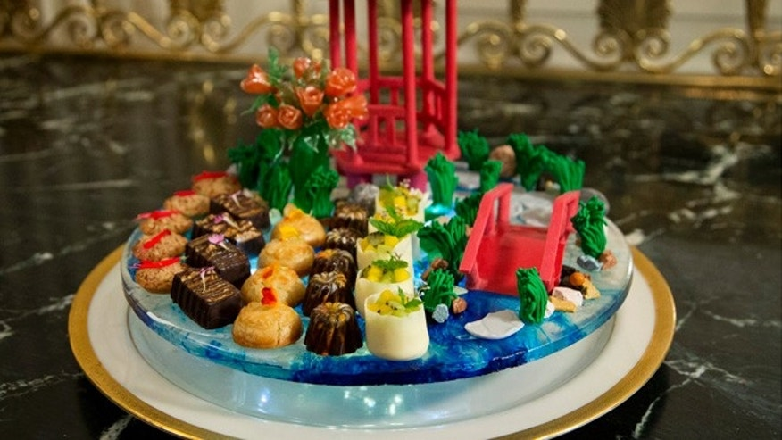 "Sept. 24, 2015: The dessert called ""a stroll through the garden"" composed of handmade chocolate pavilion and bridge, pulled sugar roses, and white lotus flowers, that symbolize good fortune, is shown during a preview in the State Dining Room of White House in Washington for the state dinner of the visiting Chinese President Xi Jinping.(AP)"