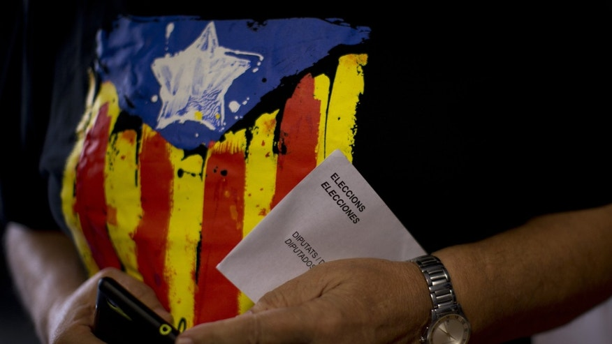 A man holds his ballot paper before voting at a polling station in Barcelona, Spain, Sunday Sept. 27, 2015. Voters in Catalonia go to the polls on Sunday to elect regional lawmakers, with pro-secession parties saying they will push for independence within 18 months if they win a majority in the 165-seat parliament, as most opinion polls predict they will. (AP Photo/Emilio Morenatti)