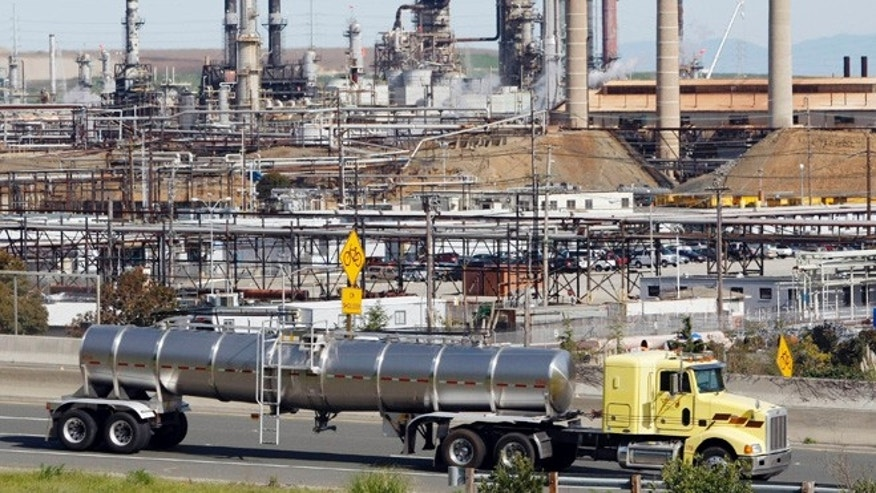 In this March 9, 2010 file photo, a tanker truck passes an oil refinery in Richmond, Calif.