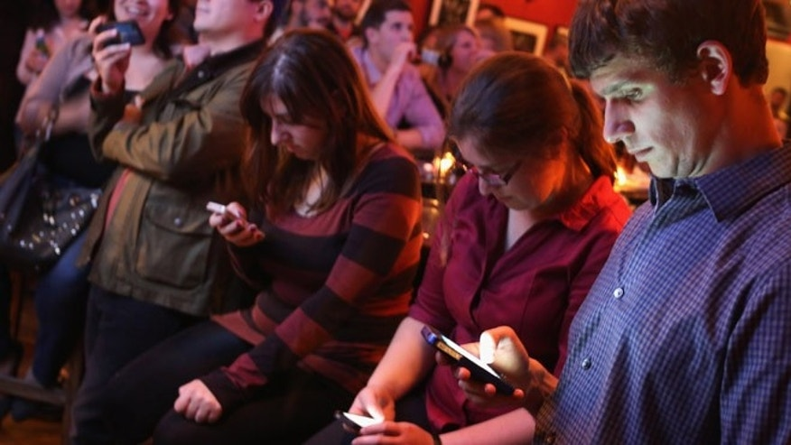 Young adults split their time between the televised debate and their smart phones during a debate watch party at the Local 16 bar and restaurant October 13, 2015 in Washington, DC. (Photo by Chip Somodevilla/Getty Images)