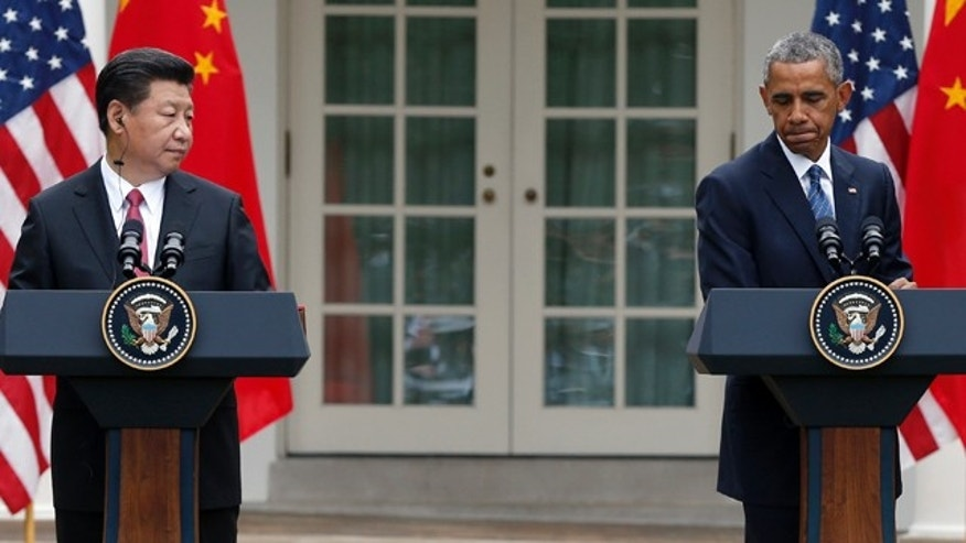 FILE - In this Friday, Sept. 25, 2015, file photo, President Barack Obama, right, pauses during a joint news conference with Chinese President Xi Jinping in the Rose Garden of the White House in Washington. (AP Photo/Evan Vucci, File)