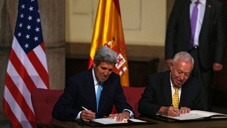 U.S. Secretary of State John Kerry, left, and Spain's Foreign Minister Jose Manuel Garcia Margallo sign agreements at the Santa Cruz palace, Spain's Foreign Affairs Ministry, in Madrid, Spain, Monday, Oct. 19, 2015. Spain and the United States signed an agreement Monday to further discuss the cleanup and removal of land contaminated with radioactivity after a mid-air collision in 1966 dumped four U.S. hydrogen bombs near the southern Spanish village of Palomares. (AP Photo/Francisco Seco)