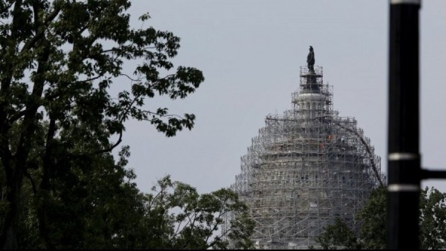 A pedestrian red light is seen near the U.S. Capitol dome, currently under renovation, in Washington June 8, 2015. (REUTERS/Carlos Barria)