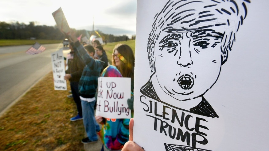 People hold signs during a silent protest of Republican presidential candidate Donald Trump in Sioux City, Iowa, Tuesday, Oct. 27, 2015. Hundreds of students, parents and other Sioux City residents protested Trump's appearance at a northwestern Iowa high school on Tuesday, saying the Republican presidential candidate's rhetoric about immigrants violates the school's anti-bullying policy. (Justin Wan/Sioux City Journal via AP) MANDATORY CREDIT