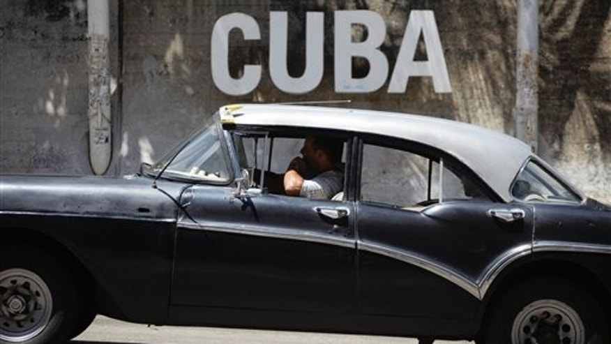 "A man drives his taxi past a Cultural Center with the word ""Cuba"" on it, in Havana, Cuba, Tuesday, April 14, 2015."